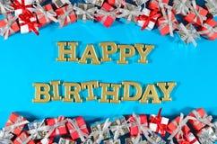 Texte d'or de joyeux anniversaire et cadeaux argentés et rouges sur un bleu image libre de droits