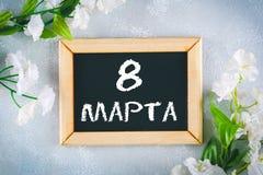 Texte dans le Russe : 8 mars Tableau noir et fleurs blanches Jour international du ` s de femmes Images libres de droits