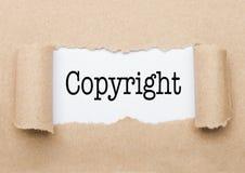 Texte de Copyright paraissant derrière le papier brun déchiré images stock
