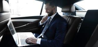 Texte de dactylographie d'homme d'affaires sur l'ordinateur portable tout en se reposant dans la voiture Photo stock