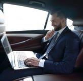 Texte de dactylographie d'homme d'affaires sur l'ordinateur portable tout en se reposant dans la voiture Image libre de droits