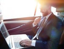 Texte de dactylographie d'homme d'affaires sur l'ordinateur portable tout en se reposant dans la voiture Photos stock