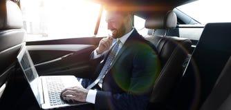 Texte de dactylographie d'homme d'affaires sur l'ordinateur portable tout en se reposant dans la voiture Photos libres de droits