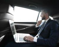 Texte de dactylographie d'homme d'affaires sur l'ordinateur portable tout en se reposant dans la voiture Images libres de droits