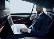 Texte de dactylographie d'homme d'affaires sur l'ordinateur portable tout en se reposant dans la voiture Images stock
