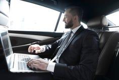 Texte de dactylographie d'homme d'affaires sur l'ordinateur portable tout en se reposant dans la voiture Photographie stock libre de droits