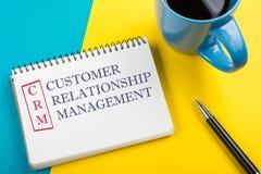 Texte de gestion de relation de client de CRM écrit sur la page de carnet, le stylo et la tasse de café Photos libres de droits