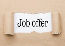 Texte de Job Offer paraissant derrière le papier brun déchiré images stock