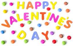 Texte de jour de valentines heureux de lettres colorées parmi les bonbons ronds multicolores D'isolement Image libre de droits