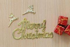 Texte de Joyeux Noël d'or et boîte-cadeau rouge sur un flo en bois brun Photographie stock