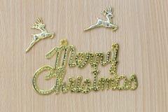 Texte de Joyeux Noël d'or sur un plancher en bois brun Photographie stock