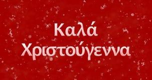 Texte de Joyeux Noël dans le Grec sur le fond rouge Photo stock