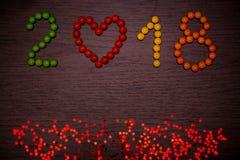 Texte de la bonne année 2018 des sucreries colorées sur le fond en bois Photographie stock
