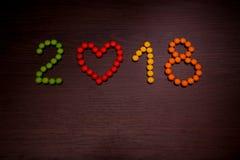 Texte de la bonne année 2018 des sucreries colorées sur le fond en bois Photo libre de droits