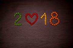Texte de la bonne année 2018 des sucreries colorées sur le fond en bois Images stock