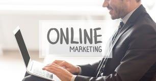 Texte de marketing en ligne contre l'homme d'affaires travaillant sur l'ordinateur portable Photographie stock