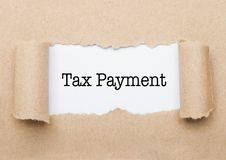 Texte de paiement d'impôts paraissant derrière le papier brun déchiré image stock