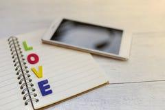Texte en bois coloré d'amour au-dessus de carnet vide Image stock