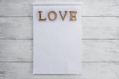 Texte en bois d'amour au-dessus de bloc-notes vide Photos stock