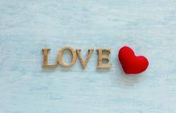 Texte en bois d'amour et coeur rouge au-dessus de fond bleu Images libres de droits