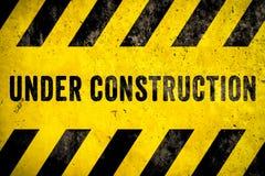 Texte en construction de panneau d'avertissement avec les rayures noires jaunes peintes au-dessus du fond de texture de façade de photographie stock