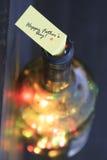Texte et bouteille heureux de jour de pères avec les lumières colorées Photos stock