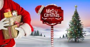 Texte et Santa de Joyeux Noël tenant des cadeaux avec le poteau indicateur en bois dans le paysage d'hiver de Noël avec illustration libre de droits