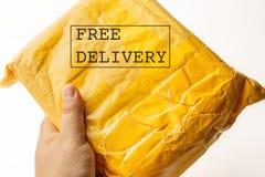 Texte GRATUIT de la LIVRAISON sur le paquet de colis ou la boîte jaune de cargaison avec le produit dans la main masculine, expéd photo libre de droits