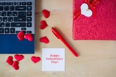 Texte heureux de jour du ` s de Valentine écrit sur l'autocollant à la table Photographie stock
