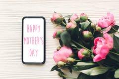 Texte heureux de jour du ` s de mère sur l'écran de téléphone et les pivoines roses sur la rouille Photographie stock libre de droits