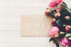 Texte heureux de jour du ` s de mère sur la carte et le bouquet rose o de métier de pivoines Photographie stock