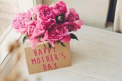 Texte heureux de jour du ` s de mère sur la carte et le bouquet rose o de métier de pivoines Photos stock