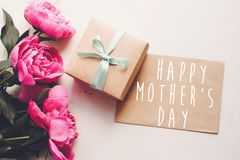 Texte heureux de jour du ` s de mère sur la carte et le bouquet rose W de métier de pivoines Photo stock