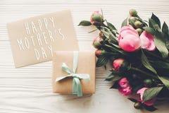Texte heureux de jour du ` s de mère sur la carte et le bouquet rose W de métier de pivoines Photo libre de droits