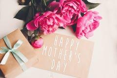 Texte heureux de jour du ` s de mère sur la carte et le bouquet rose W de métier de pivoines Photographie stock libre de droits