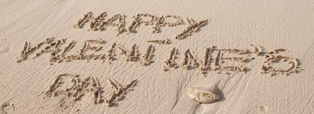 Texte heureux du jour de valentine écrit sur le sable images stock