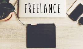 Texte indépendant sur le bureau en bois avec l'ordinateur portable, comprimé graphique, notebo Image stock