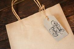 Texte noir de calligraphie de vendredi sur l'étiquette de papier d'emballage avec le paquet vide pour le texte et le fond en bois Photos stock