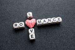 Texte roman de bloc de mots croisé d'amour avec le coeur rose de fil sur l'obscurité images stock