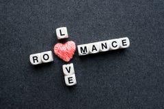 Texte roman de bloc de mots croisé d'amour avec le coeur rose de fil sur l'obscurité Photo stock