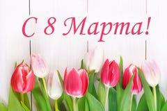 Texten i ryss: från 8 mars Internationell dag för kvinna` s Tulpan på en vit trätabell Fotografering för Bildbyråer