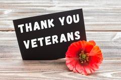 Texten tackar dig veteran som är skriftliga i en svart tavla och en röd vallmo på en lantlig träbakgrund Royaltyfria Bilder