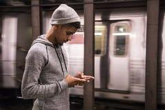 Texter för en ung man på hans smarta telefon, som han väntar på en NYC-subwa fotografering för bildbyråer