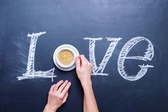Textförälskelse som skriver vid bästa sikt för kritakaffekopp Royaltyfria Foton