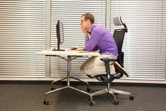 Texthals - man, i att sitta hopsjunken positionen som arbetar med datoren Royaltyfri Bild