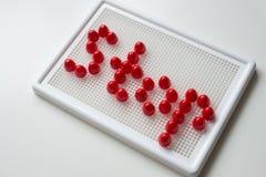 Texthalt umrissen mit Mosaiken Die Rotbuchstaben und das weiße backg Lizenzfreie Stockfotos