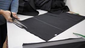 Textiel, arbeider van de zwarte stof van atelierbesnoeiingen op witte lijst stock footage