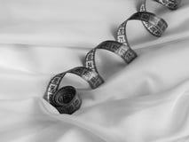 Textiel met gordijn en verdraaid meetlint, zwart-wit schot stock fotografie