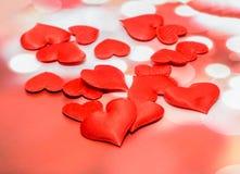 Textiel rode harten, de harten van de Valentijnskaartendag, rode bokehachtergrond Stock Fotografie