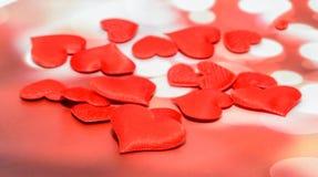 Textiel rode harten, de harten van de Valentijnskaartendag, rode bokehachtergrond Royalty-vrije Stock Afbeelding